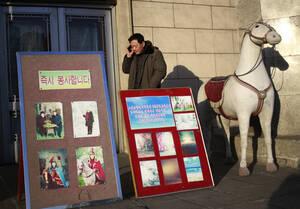Ένας άντρας μιλάει στο κινητό του έξω από ένα φωτογραφείο.