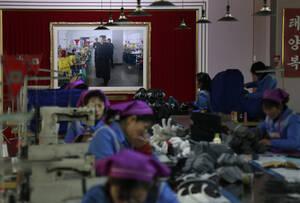 Εργοστάσιο κατασκευής αθλητικών παπουτσιών. Στον τοίχο, ο Κιμ...
