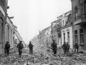1945 Βρετανοί στρατιώτες προελαύνουν προσεκτικά σε έναν δρόμο γεμάτο συντρίμμια από τους βομβαρδισμούς, στη γερμανική πόλη Γκοχ, που πλέον βρίσκεται σε συμμαχικά χέρια.