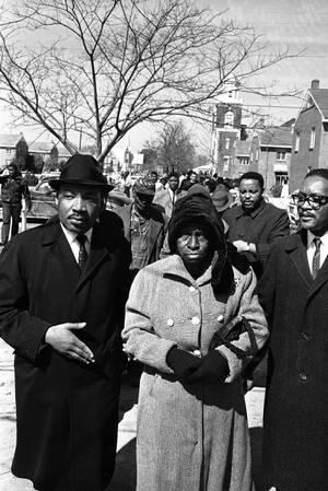 1965 Ο Μάρτιν Λούθερ Κινγκ φεύγει από μια εκκλησία στην Αλαμπάμα, αφού έχει παρακολουθήσει τη λειτουργία. Κατευθύνεται στο δικαστήριο για να παραστεί στη δίκη Αφροαμερικανών που συνελήφθησαν κατά τη διάρκεια διαδηλώσεων υπέρ ου δικαιώματος των μαύρων να
