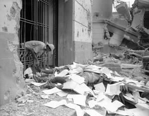 1945 Ένας Φιλιππινέζος βγάζει τα παπούτσια ενός νεκρού Ιάπωνα στρατιώτη, στην ολοσχερώς κατεστραμένη από τις μάχες Μανίλα.