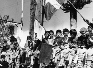 1956 Παιδιά κρατούν σημαίες και περιμένουν τον Αρχιεπίσκοπο Μακάριο να περάσει καθ' οδόν για το αεροδρόμιο της Λευκωσίας, απ' όπου θα έφευγε για την Ελλάδα. Τελικά συνελήφθη στο αεροδρόμιο και στάλθηκε εξορία στις Σεϋχέλλες.
