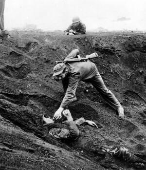 1945 Ένας Αμερικανός πεζοναύτης πλησιάζει έναν Ιάπωνα στρατιώτη στην Ίβο Ζίμα. Ο Ιάπωνας στρατιώτης ήταν θαμμένος επί μιάμιση μέρα σε έναν κρατήρα, παριστάνοντας το νεκρό και έχοντας μια χειροβομβίδα δίπλα του. Οι πεζοναύτες φοβήθηκαν ότι είχε και άλλα ε