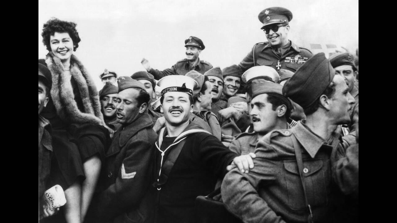 """1949 Η βασίλισσα Φρειδερίκη (αριστερά) και ο βασιλιάς Παύλος της Ελλάδας στους ώμους ανδρών που κρατούνται στη Μακρόνησο. Οι άνδρες αυτοί βρίσκονται στο νησί προκειμένου να """"αναμορφωθούν"""", καθώς είναι όλοι τους πρώην Κομμουνιστές. Κάποιοι από αυτούς θα κ"""