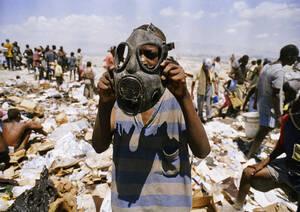 1995 Ένα αγόρι στην Αϊτή φοράει μια αμερικανική μάσκα που βρήκε ανάμεσα σε άλλα αντικειμενα στη χωματερή του πορτ Ο Πρενς. Οι Αϊτινοί ψάχνουν στα σκουπίδια των Αμερικάνων διαρκώς, καθώς υποφέρουν από έλλειψη βασικών αγαθών. Οι Αμερικάνοι βρίσκονται στη χ