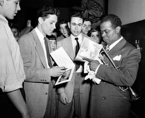 1948 Ο τρομπετίστας της τζαζ, Λούις Άρμστρονγκ (δεξιά) υπογράφει αυτόγραφα στο κλαμπ Blue Note, στο Σικάγο, μετά από μια συναυλία. Οι νεαροί που είναι μαζί του έφτασαν στο Σικάγο από το Μιλγουόκι με οτο-στοπ για να τον παρακολουθήσουν.
