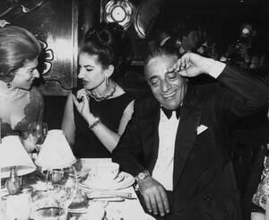"""1965 Η σοπράνο Μαρία Κάλλας, στο κέντρο συνομιλεί με μια φίλη της, ενώ ο Αριστοτέλης Ωνάσης κάνει νόημα στους φωτογράφους, οι δύο τους παρακολουθούν ένα γκαλά στο Maxim, στο Παρίσι, λίγο πριν την πρεμιέρα στη Γαλλία της ταινίας """"Ζορμπάς""""."""