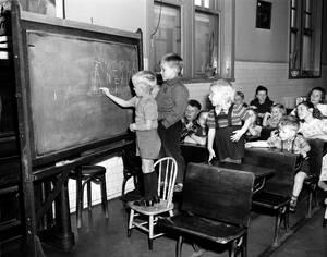 """1949 Τρία παιδιά από τη Φινλανδία γράφουν τη λέξη """"Αμερική""""¨στο μαυροπίνακα, σε τάξη παιδιών μεταναστών, στο Έλις Άιλαντ της Νέας Υόρκης, Οι ηλικίες τους είναι από 3 έως 11 ετών."""
