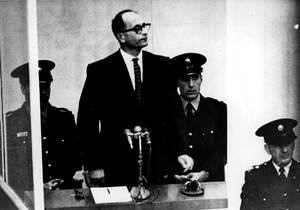 1961 Ο Άντολφ Άιχμαν στέκεται πίσω από ένα αλεξίσφαιρο τζάμι στο δικαστήριο στην Ιερουσαλήμ, την πρώτη μέρα της δίκης του για γενοκτονία.