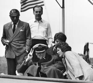 """1961 Ο πρώην Πρωθυπουργός της Βρετανίας Ουίνστον Τσόρτσιλ χαιρετάει τη Νέα Υόρκη από το κατάστρωμα της θαλαμηγού """"Χριστίνα"""". Ο ιδιοκτήτης της θαλαμηγού, Αριστοτέλης Ονάσης στέκεται πίσω από τον Τσόρτσιλ, με ένα ποτό στο χέρι."""