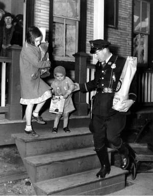 1935, Νιού Τζέρσεϊ.  Ένας αστυνομικός βοηθάει ένα παιδί να κατέβει τη σκάλα σε σημείο όπου μοιράζονται τρόφιμα στους φτωχούς, κατά τη διάρκεια της μεγάλης κρίσης.