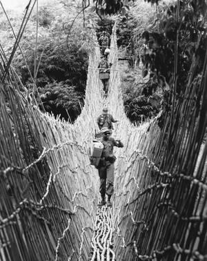 1966, Βιετνάμ.  Αμερικανοί στρατιώτες των ειδικών δυνάμεων διασχίζουν μια κρεμαστή γέφυρα, φτιαγμένη από μπαμπού, πάνω από ένα ρέμα στη ζούγκλα του κεντρικού Βιετνάμ. Αποστολή τους είναι να βρεθούν στα υψίπεδα του κεντρικού Βιετνάμ και να προσπαθήσουν να