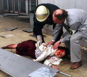 1985, Φρανκφούρτη.  Ένας πυροσβέστης και ένας διασώστης βοηθούν μια τραυματισμένη γυναίκα μετά την έκρηξη βόμβας στο αεροδρόμιο της Φρανκφούρτης.