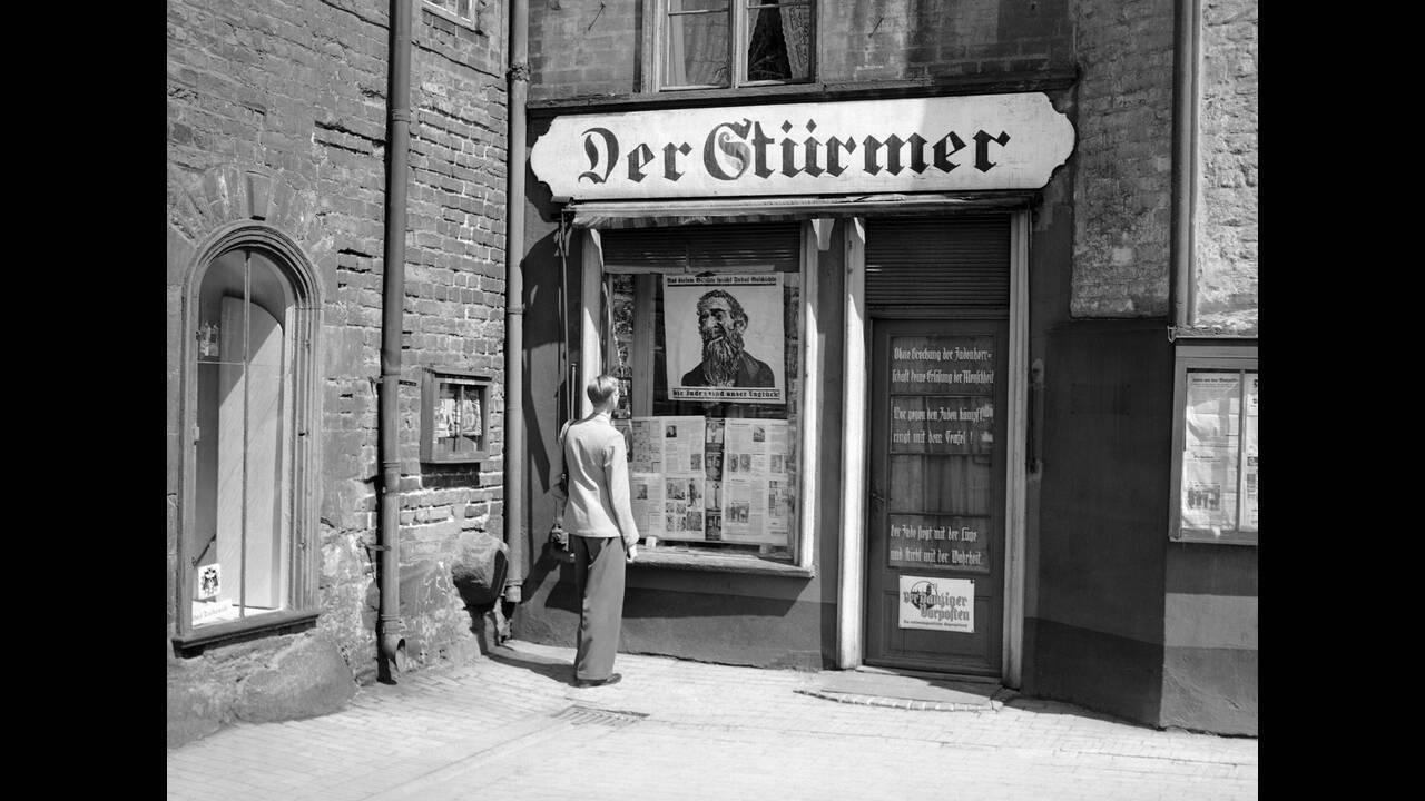 1939, Ντάντζιγκ.  Ένας άνδρας παρατηρεί τη γκροτέσκα απεικόνιση ενός Εβραίου στο παράθυρο της αντι-εβραϊκής εφημερίδας Der Sturmer, στο Ντάντζιγκ (σημερινό Γκντανσκ). Όπως σε όλα τα μέρη που βρίσκονται υπό τη ναζιστική κυριαρχία, η αντι-εβραϊκή προπαγάνδ