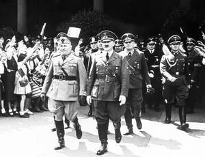 1940, Βερολίνο.  Ο Αδόλφος Χίτλερ και ο Μπενίτο Μουσολίνι περνούν μπροστά από παιδιά που χαιρετάνε φασιστικά, μετά από τη συνάντησή τους στο Βερολίνο.
