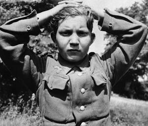 1944, Γαλλία.  Με τα χέρια πάνω από το κεφάλι, ένας Γερμανός στρατιώτης, μολις 16 ετών, είναι ανάμεσα στους Γερμανούς που παραδόθηκαν στις συμμαχικές δυνάμεις μετά την απόβαση στη Νορμανδία.
