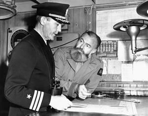1944.  Ο Ερνστ Χέμινγουεϊ (δεξιά) με τον πλοίαρχο ενός μεταγωγικού πλοίου, κοιτούν τους χάρτες με τα σχέδια της απόβασης σε νησιά του Ειρηνικού.