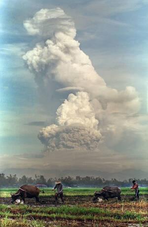 1991, όρος Πινατούμπο. Φιλιππινέζοι αγρότες  στα ορυζοχώραφα στο Σαν Φερνάντο στις Φιλιππίνες συνεχίζουν να εργάζονται, όσο το ηφαίστειο Πινατούμπο βγάζει καπνούς και στάχτη.