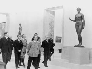 1938, Βερολίνο.  Ο Φίρερ, Αδόλφος Χίτλερ και ο υπουργός Προπαγάνδας του Ράιχ, Γιόζεφ Γκέμπελς, επισκέπτονται μια έκθεση γερμανικής Τέχνης. Ο Χίτλερ εγκαινίασε την έκθεση.