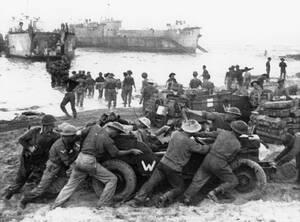 Σικελία, 1943. Στρατιώτες των συμμάχων σπρώχνουν ένα τζιπ, ενώ άλλοι ξεφορτώνουν στρατιωτικό υλικό και οχήματα, σε μια ακτή της Σικελίας κατά τη διάρκεια της απόβασης.