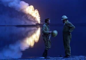Κουβέιτ, 1991. Αμερικανοί πυροσβέστες συζητούν στο τέλος μιας δύσκολης ημέρας, όσο μια πετρελαιοπηγή καίγεται ανεξέλεγκτα στο βάθος. Περισσότερες από 700 πετρελαιοπηγές παραδόθηκαν στις φλόγες από τα στρατεύματα του Ιράκ που υποχωρούσαν από το Κουβέιτ.