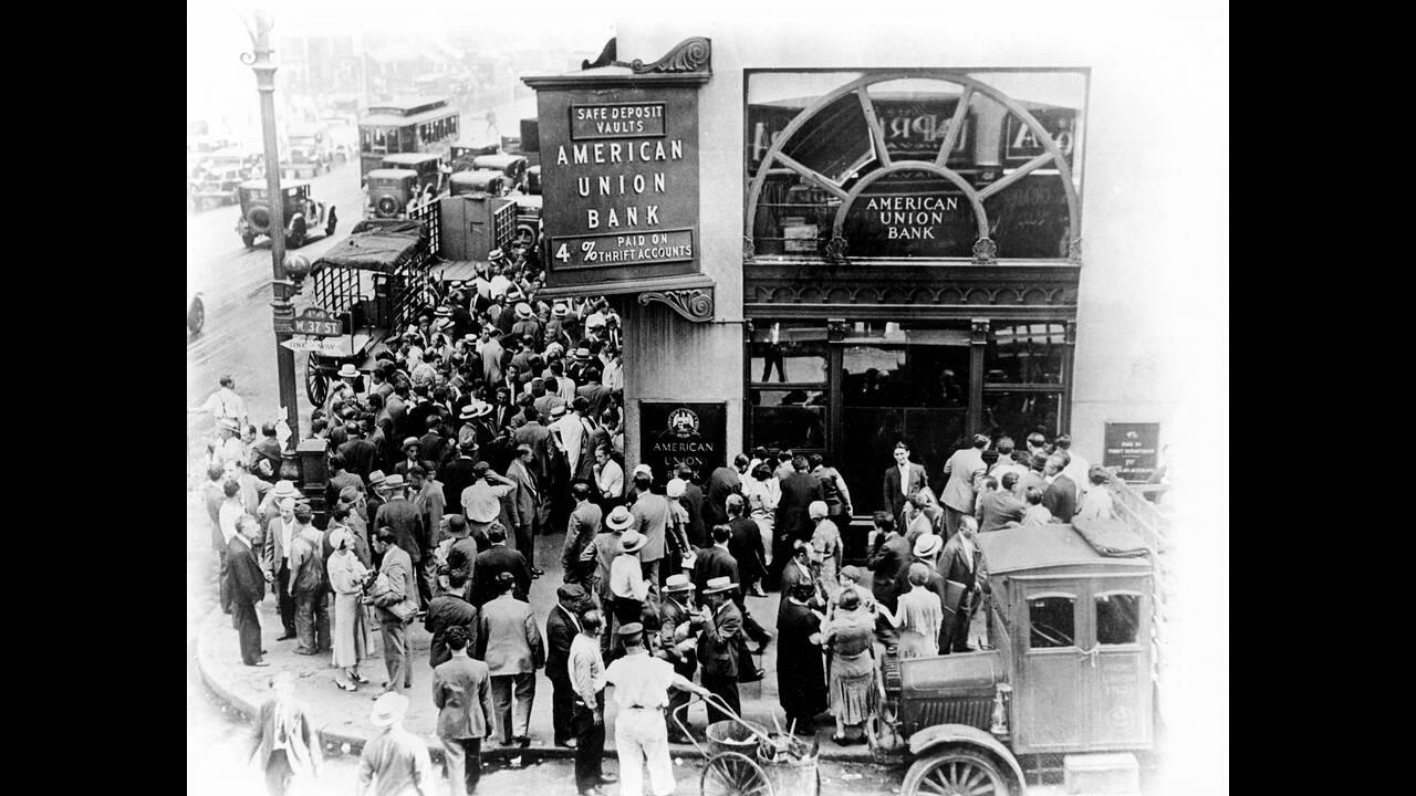 1931, Νέα Υόρκη. Καταθέτες είναι συγκεντρωμένοι έξω από τις κλειστές πόρτες της τράπεζας American Union στη Νέα Υόρκη. Είναι μια από τις μικρότερες τράπεζες της πόλης που υπέστησαν υποτίμηση των καταθέσεων και έκλεισαν με διαταγή της κρατικής υπηρεσίας επ
