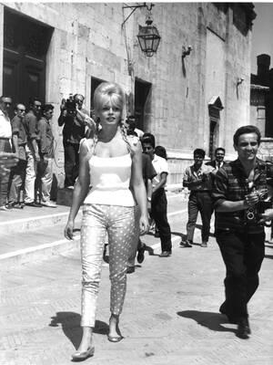 """1961, Σπολέτο. Η Γαλλίδα ηθοποιός Μπριζίτ Μπαρντό περπατάει στους δρόμους της μικρής ιταλικής πόλης. Βρίσκεται εδώ για τα γυρίσματα της ταινίας """"Private Life"""" και φοράει το χαρακτηριστικό της παντελόνι κάπρι και μια κοντή μπλούζα..."""