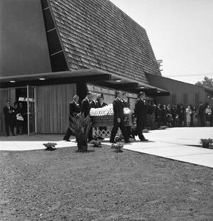 1962, Χόλιγουντ. Το φέρετρο με το άψυχο σώμα της Μέρλιν Μονρόε μεταφέρεται από το περεκκλήσι στο οποίο εψάλη η νεκρώσιμος ακολουθία, στην κρύπτη στην οποία θα ταφεί.