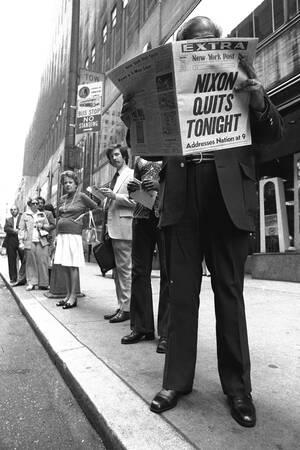 1974, Νέα Υόρκη. Άνθρωποι περιμένουν για το λεωφορείο και διαβάζουν στην εφημερίδα τα νέα για την απόφαση του Προέδρου Νίξον να παραιτηθεί.