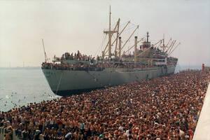 1991, Μπάρι. Χιλιάδες Αλβανοί που έφυγαν από τη χώρα τους για να ξεφύγουν από τη φτώχεια και συχνά την πείνα, στιβάζονται στο λιμάνι του Μπάρι, περιμένοντας να ζητήσουν άσυλο στην Ιταλία.