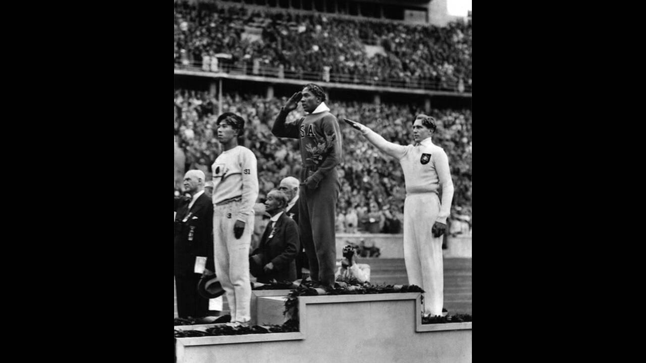 1936, Βερολίνο. Ο Αμερικανός αθλητής Τζέσε Όουενς  (στο κέντρο) έτοιμος να δεχτεί το χρυσό μετάλλιο που κέρδισε στο άλμα εις μήκος στους Ολυμπιακους Αγώνες του Βερολίνου. Ο Όουενς κέρδισε τέσσερα μετάλλια στους Αγώνες.