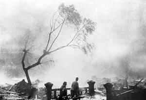 1945, Ναγκασάκι. Επιζήσαντες της ατομικής έκρηξης στο Ναγκασάκι περπατουν ανάμεσα στα ερείπια, καθώς πίσω τους μαίνεται η φωτιά.