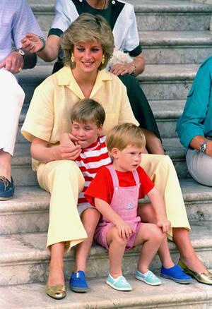 1987, Μαγιόρκα. Η πριγκίπισσα Νταϊάνα με τους γιους της, Χάρι και Ουίλιαμ, στα σκαλιά του παλατιού στη Μαγιόρκα, όπου κάνουν διακοπές, καλεσμένοι τηςισπανικής βασιλικής οικογένειας.