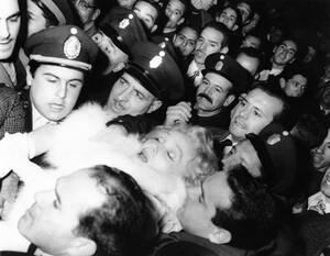 1959, Μπουένος Άιρες. Η Μαρλέν Ντίτριχ μεταφέρεται από αστυνομικούς έξω από την Όπερα του Μπουένος Άιρες, όπου λιποθύμησε, περικυκλωμένη ασφυκτικά από το πλήθος των θαυμαστών της.