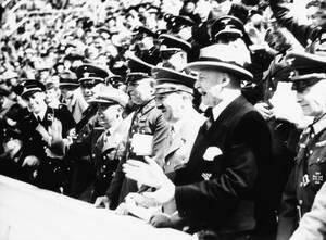 1936, Βερολίνο. Ο Γερμανός Καγγελάριος, Αδόλφος Χίτλερ, ο οποίος παρακολουθεί  κάθε μέρα τους Ολυμπιακούς Αγώνες , δείχνει ευχαριστημένος με τον τρόπο που εξελίσσονται οι Αγώνες. Στα αριστερά του είναι ο Δρ. Θίοντορ Λέβαλντ, Πρόεδρος της γερμανικής Ολυμπ