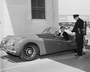 """1950, Χόλιγουντ. Ο ηθοποιός Κλαρκ Γκέιμπλ μιλάει με τον θυρωρό των στούντιο στα οποία γυρίζεται η ταινία του, """"To Please A Lady"""". Οδηγεί μια Jaguar XK120."""