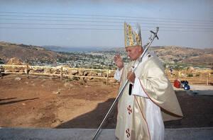 1990, Τανζανία. Ο πάπας Ιωάννης Παύλος ο Β' κατευθύνεται στο βάθρο από το οποίο θα απευθυνθεί στο πλήθος, στη Μουάνζα της Τανζανίας. Στο βάθος διακρίνεται η λίμνη Βικτώρια. Τη λειτουργία θα παρακολουθήσουν περισσότεροι από 50.000 άνθρωποι.