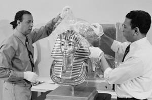 1976, Ουάσινγκτον. Τα προστατευτικά καλύματα αφιαρούνται από τη μάσκα του Τουταγχαμών, του νεαρού βασιλιά της Αιγύπτου (1334-1325 π.Χ.), από δύο εργάτες στην Εθνική Πινακοθήκη της Ουάσινγκτον. Η μάσκα του Τουταγχαμών, μαζί με 55 ακόμα θησαυρούς από τον τά