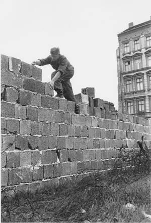 1961, Ανατολικό Βερολίνο. Ένας Ανατολικογερμανός αστυφύλακας προσθέτει τούβλα στο τείχος του Βερολίνου, το οποίο πρόκειται να φτάσει τα πέντε μέτρα σε ύψος.