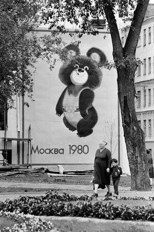 1979, Μόσχα. Μια γυναίκα και ο εγγονός της περπατούν μπροστά από μια αφίσα με το Μίσα, τη μασκότ των Ολυμπιακών Αγώνων της Μόσχας, που θα γίνουν το 1980.