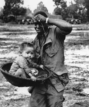 1966, Βιετνάμ. Ένα νεαρό αγόρι κρατιέται καθώς μεταφέρεται σε ένα καλάθι από Αμερικανικό αλεξιπτωτιστή προς το ελικόπτερο που θα τον πάρει από το χωριό του στο Xuan Loc, περίπου 120 χιλιόμετρα βορειοανατολικά της Σαιγκόν, σε ένα νέο χωριό. Η μητέρα του πα