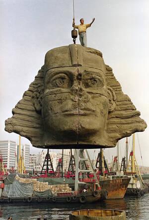 1991, Χονγκ Κονγκ. Ένα αντίγραφο της κεφαλής της Σφίγγας φορτώνεται σε πλοίο στο λιμάνι του Χονγκ Κονγκ για να μεταφερθεί στην Αίγυπτο. Είναι μέρος του σκηνικού που θα στηθεί για την όπερα Αΐντα του Βέρντι, η οποία θα παιχτεί κάτω από τις πυραμίδες.