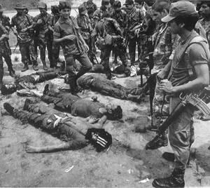 1988, Ελ Σαλβαδόρ. Οι στρατιώτες της φρουράς στο El Paraiso στο βόρειο Ελ Σαλβαδόρ κοιτούν τα πτώματα των ανδρών που σκοτώθηκαν κατά τη διάρκεια μιας επιδρομής ανταρτών στη βάση. Εννέα στρατιώτες και επτά αντάρτες έχασαν τη ζωή τους στη δίωρη μάχη.