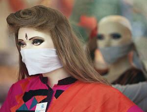 1994, Νέο Δελχί. Μια κούκλα, φορώντας μάσκα, διαφημίζει ρούχα μπροστά σε ένα γυναικείο κατάστημα ειδών ένδυσης στο Νέο Δελχί. Πολλοί κάτοικοι ττης πόης έχουν αρχίσει να φορούν τις μάσκες μετά από τους πρώτους δύο θάνατους στο Νέο Δελχί πόλης από πνευμονικ