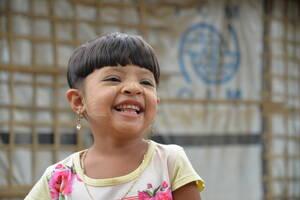 Η Αμούντια, 5 ετών, είναι Ροχίνγκια από την πολιτεία Ρακάιν της Μιανμάρ. Ήρθε στον καταυλισμό στο Κοξ Μπαζάρ στις 25 Αυγούστου 2017 με τους γονείς της, τον αδελφό της και τις δύο αδελφές της, για να γλιτώσουν από τις «εκκαθαριστικές επιχειρήσεις» των δυνά