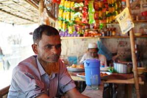 Ο Μοχαμάντ Αμίν, πρόσφυγας Ροχίνγκια που ήρθε στο Μπανγκλαντές πριν από 12 χρόνια, κάθεται σε ένα μαγαζάκι που σερβίρει τσάι στον γιγάντιο καταυλισμό του Κουτούπαλονγκ, όπου περνάει την ώρα του μερικές φορές. «Όταν ήμασταν στη Μιανμάρ, έπρεπε να πληρώσουμ