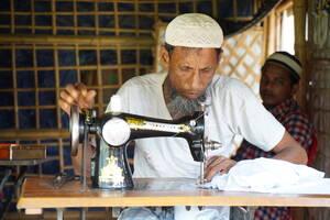 Ο Αζιζούλ Χόκε είναι ράφτης και ήρθε στο Κουτούπαλονγκ πριν από δύο χρόνια. Έφυγε από τη Μιανμάρ για να γλιτώσει από την εκτεταμένη βία κατά των Ροχίνγκια στην πολιτεία Ρακάιν. «Υποφέραμε πολύ στη Μιανμάρ, αναγκαστήκαμε να έρθουμε εδώ. Είναι δύσκολα για μ