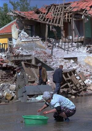 1995, Τουρκία. Μια γυναίκα πλένει τα πιάτα της σε έναν πλημμυρισμένο δρόμο στo Dinar της νοτιοδυτικής Τουρκίας, με φόντο τα ερείπια που άφησε πίσω του ο σεισμός που χτύπησε την πόλη. Τα νερά είναι από τους αγωγούς που έσπασαν κατά τη διάρκεια του σεισμού.