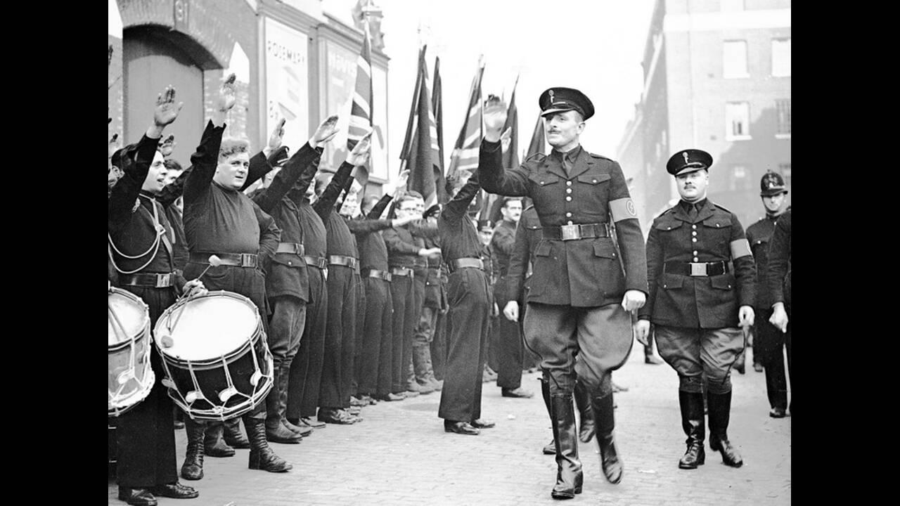 1936, Λoνδίνο. Ο Σερ Όσβαλντ Μόσλεϊ, ηγέτης των Βρετανών Φασιστών, επιθεωρεί τους μελανοχίτωνες του, στο Ανατολικό Λονδίνο. Οι φασίστες είχαν προγραματίσει πορεία στο ανατολικό Λονδίνο, η οποία όμως ματαιώθηκε, λόγω του πλήθους που διαδήλωσε εναντίον τους