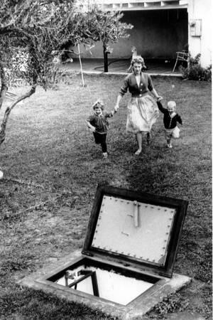1961, Σακραμέντο. Μια μητέρα και τα παιδιά της τρέχουν να μπουν στο καταφύγιο στον κήπο τους, κατά τη διάρκεια αντι-πυρηνικής άσκησης.